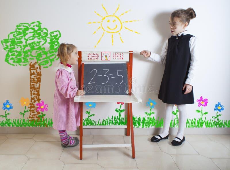 对一个更加年轻的孩子的小女孩教的数学 免版税库存照片