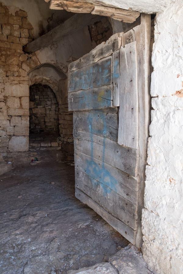 对一个被忽略的圆锥形被顶房顶的Trullo房子的内部的门在阿尔贝罗贝洛,普利亚意大利 库存图片