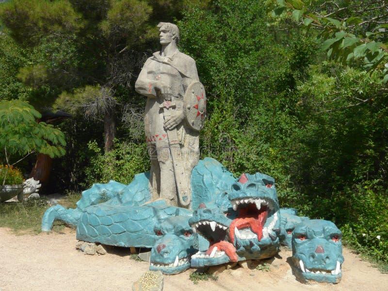 对一个骑士的一个具体雕塑有击败一条三头龙的剑的 图库摄影