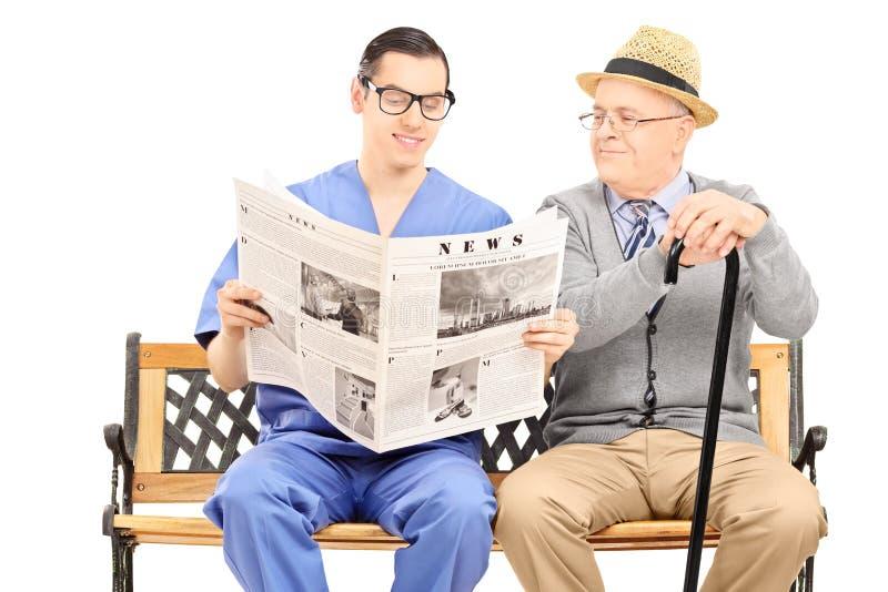 对一个年长绅士的男性护士读书报纸 免版税图库摄影