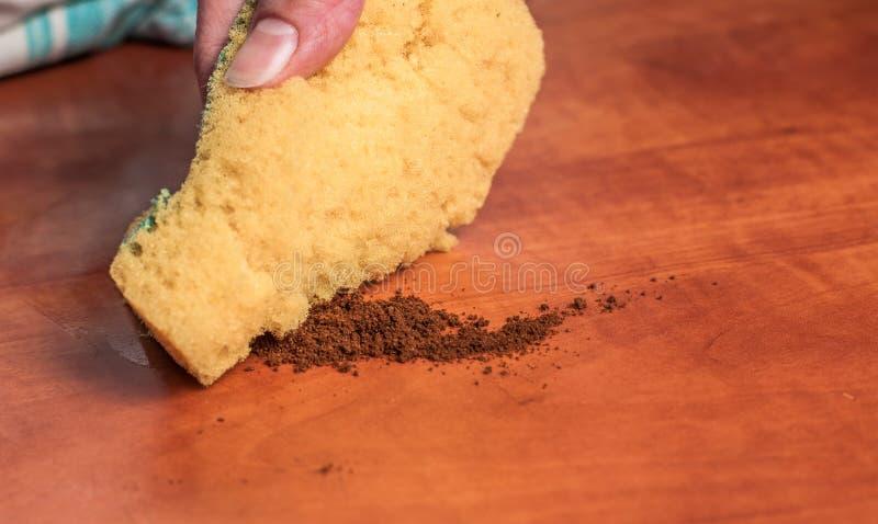 对一块黄色海绵的用途清洗厨房红色桌 清洗的海绵 免版税库存照片