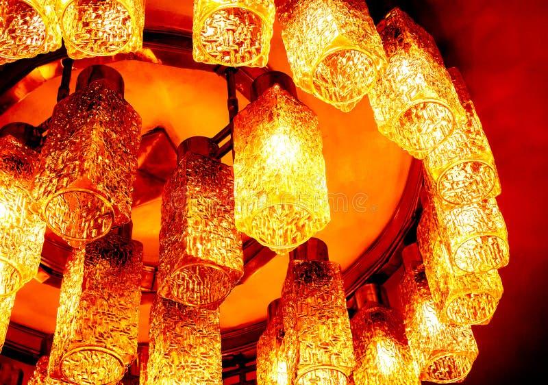对一部分的顶视图的在天花板的圆的装饰现代形状的灯反对黑暗的背景 免版税库存照片