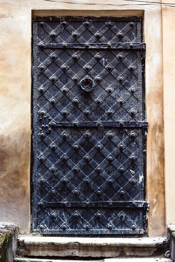 对中古的古色古香的垂直的前门 在老古老年迈的闭合的葡萄酒减速火箭的哥特式难看的东西黑色铁金属门门 库存照片