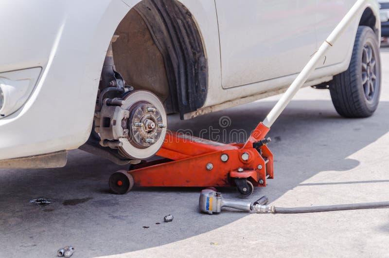 对举汽车的汽车起重器为替换轮子并且修理在gara 图库摄影