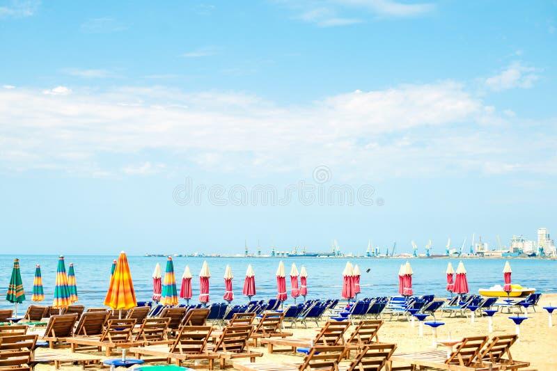 对亚得里亚海沙滩的鸟瞰图在阿尔巴尼亚,有很多伞和sunbeds,都拉斯港天际的 免版税库存照片