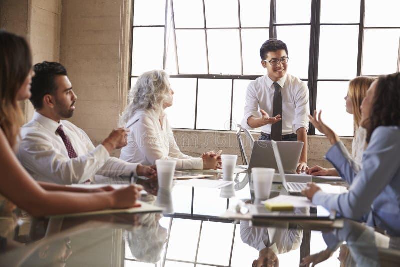 对亚洲的商人在会议,关闭同事演讲  免版税库存图片