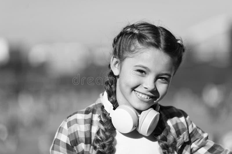 对享受音乐的声音 与无线耳机的可爱的音乐迷在脖子 使用技术的小孩为 免版税图库摄影