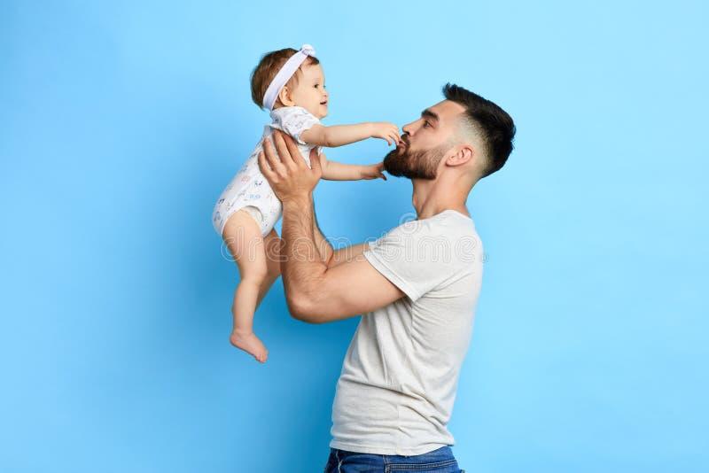 对他可爱的婴孩的年轻爸爸唱歌歌曲 免版税库存图片