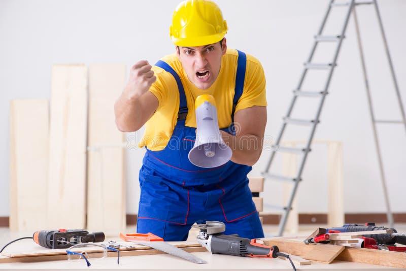 对他的工作失望的地板安装工 库存图片