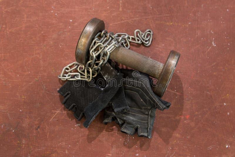 对健身染黑与银色链子的手套和半新小哑铃反对红色,橙色背景,表面 健身和健身房eq 免版税库存图片