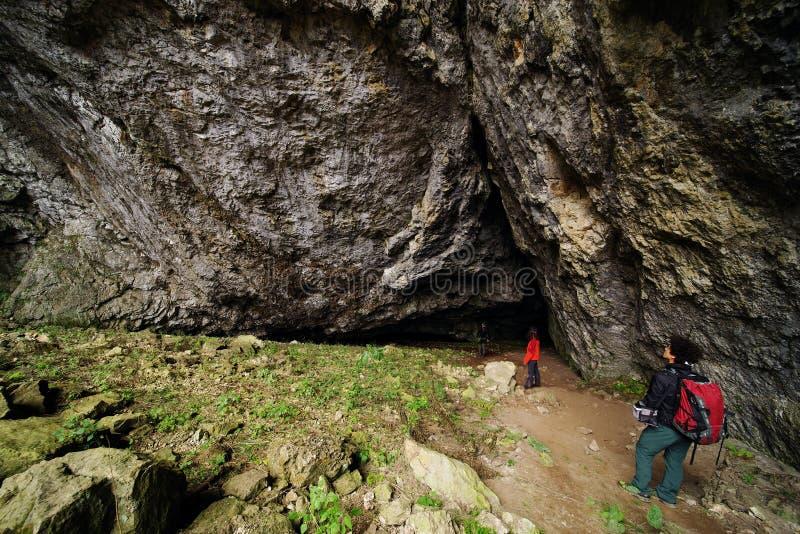 对入口的年轻夫妇在Cioclovina洞 免版税库存图片