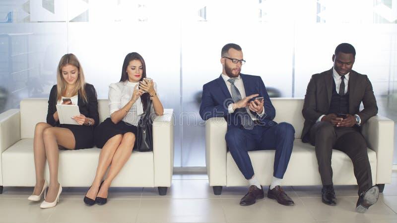 对公司的补充 年轻申请人等候采访 一个小组青年人使等待的工作不耐烦 免版税图库摄影