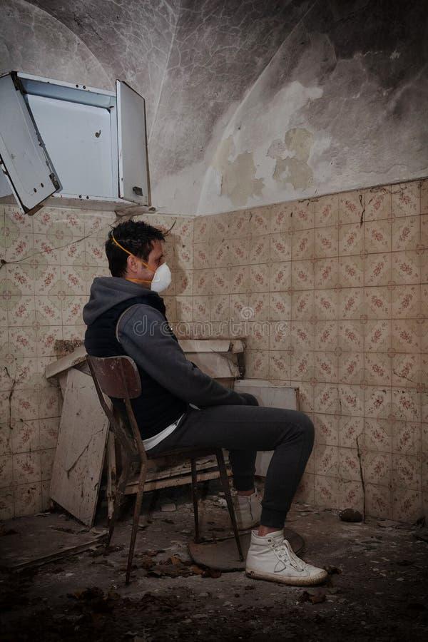 对冠状病毒的恐惧Codiv-19,一名坐在椅子上的男子,在旧的废墟中,他象征着孤独和对意大利流行病的恐惧 免版税图库摄影