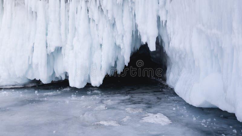 对冰洞的入口在一个春日 在贝加尔湖冰的旅行在西伯利亚 残破的冰柱 库存图片
