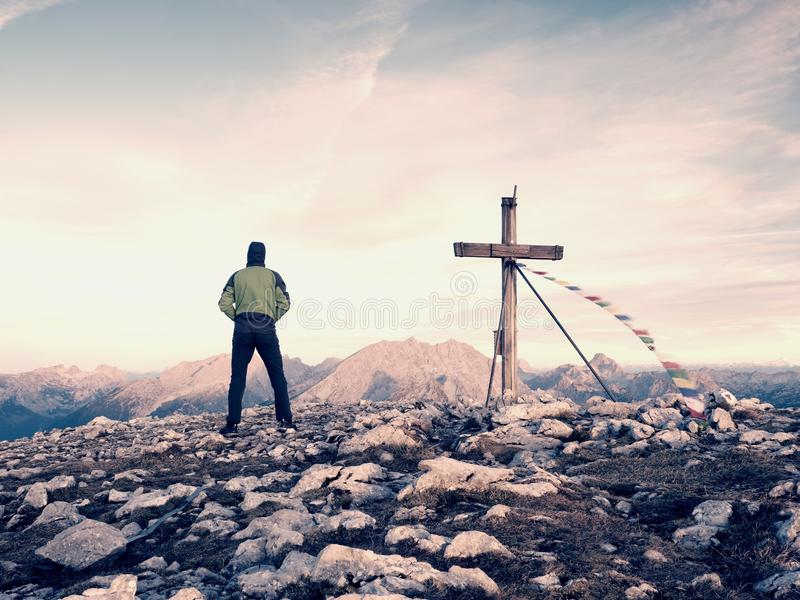 对十字架的人旅游步行在山峰 在日落期间的黑暗,五颜六色的天空 免版税库存照片