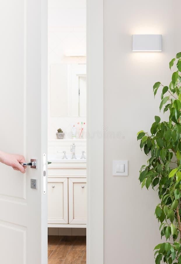 对卫生间打开门 与装饰元素的现代和明亮的内部 免版税库存照片