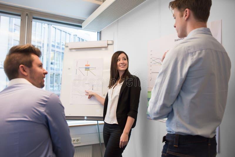 对同事的微笑的女性专业解释的图 免版税库存照片