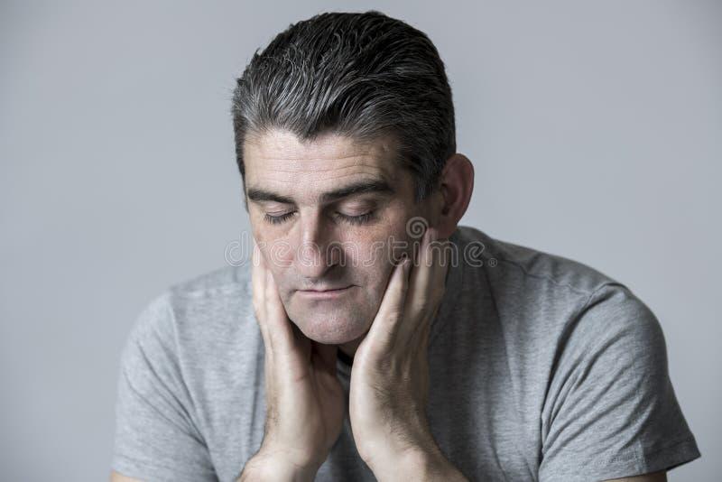 对哀伤的50s和看起来担心的人的40s挫败和体贴在灰色隔绝的担心和沉思面孔表示 库存照片