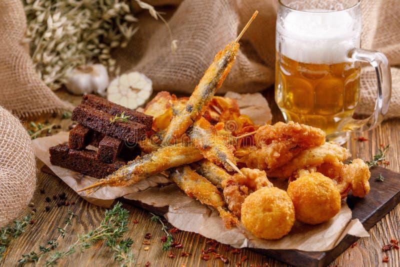 对啤酒板材的快餐 在木背景的静物画 免版税图库摄影