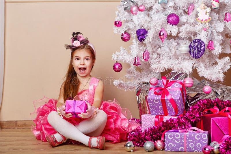 对圣诞节的一件礼物高兴的女孩 免版税图库摄影