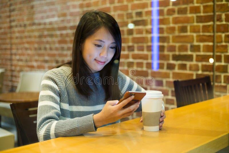 对在咖啡杯的手机的亚洲少妇用途 库存图片