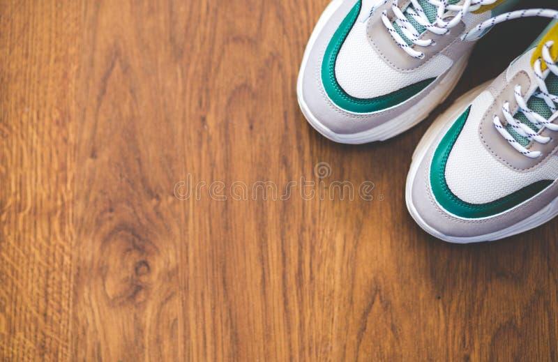 对在木背景的体育鞋子 新的运动鞋和空间广告文本的 库存图片