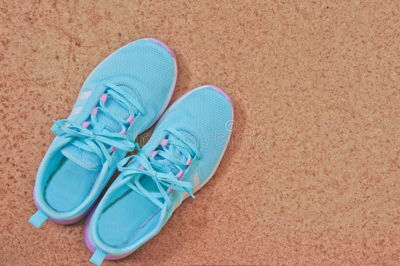 对在木背景的蓝色运动鞋 图库摄影