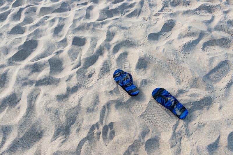 对在沙子的蓝色拖鞋 免版税库存图片