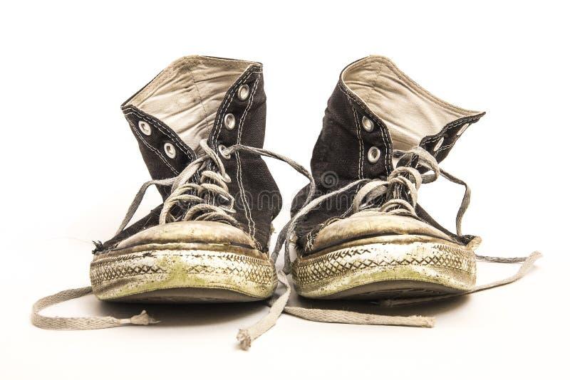 对在白色背景的人` s或少年` s穿的肮脏的难看的东西高梆的黑白高梆的网球鞋 库存图片