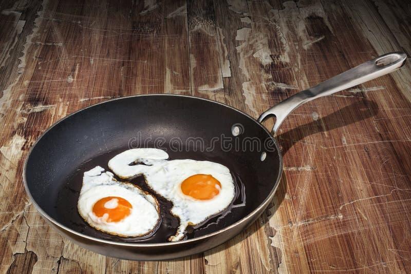 对在老耐用聚四氟乙烯煎锅准备的鸡蛋的晴朗的边设置在老破裂的片状庭院表上 免版税库存照片