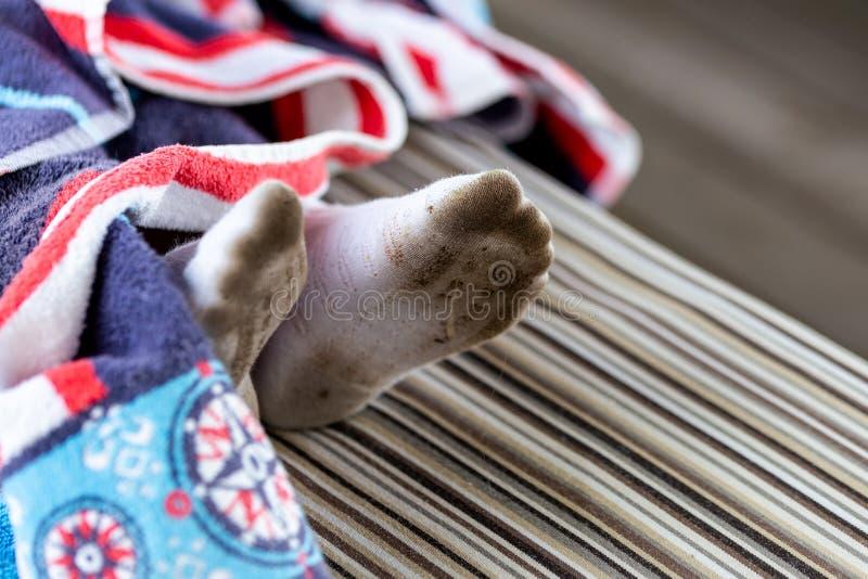 对在肮脏的被弄脏的白色袜子的儿童脚 孩子被弄脏的袜子,当使用户外时 儿童衣裳漂白的和洗涤物t 免版税库存照片
