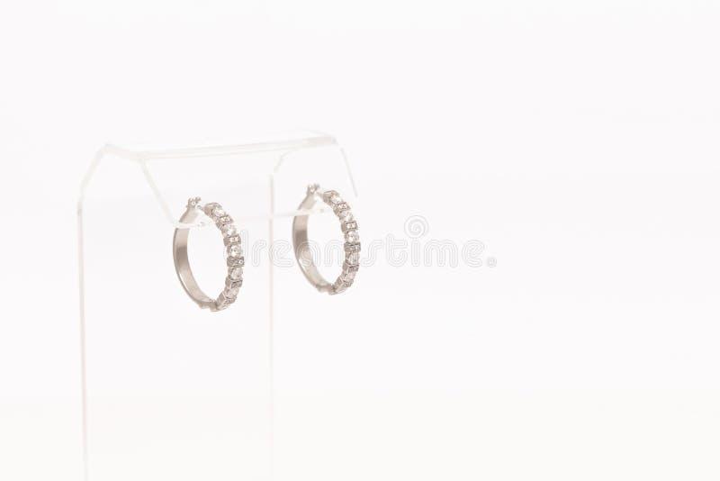 对在透明立场的白色金黄金刚石耳环 有金刚石的,豪华首饰金黄耳环 免版税库存照片