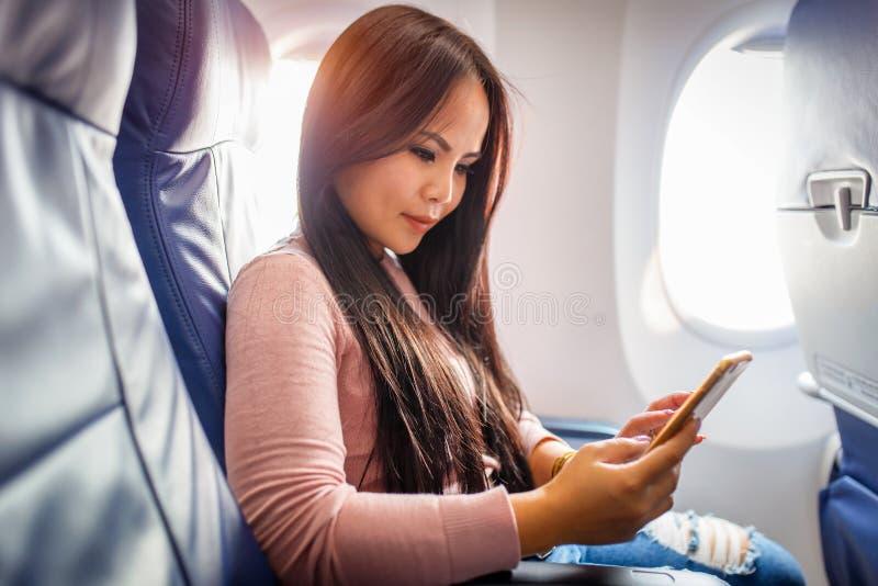 对在飞机里面的手机的亚洲妇女用途 免版税库存照片