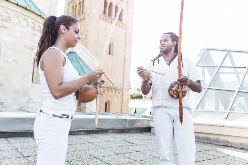 年轻对在他们的手上成为capoeira, berimbau乐器的伙伴 免版税库存图片