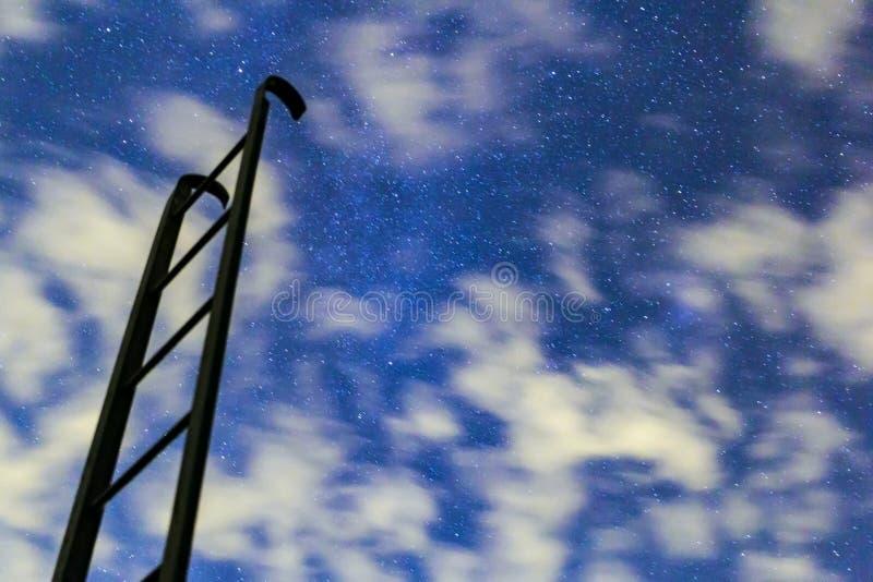 对夜满天星斗的天空的黑暗的台阶与云彩 库存照片