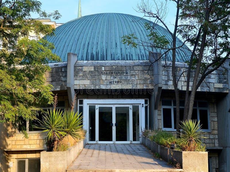 对天文馆的入口和有一个半球形的屋顶的博物馆在绿色树和丝兰中反对蓝天 免版税库存照片