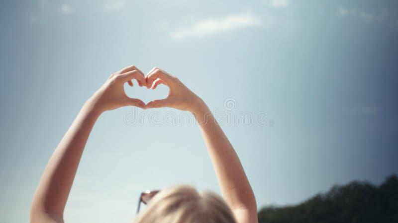 对天空的少妇上升的手在心脏形状  免版税图库摄影