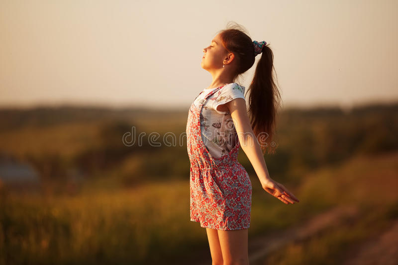对太阳的愉快的小女孩面孔 库存照片