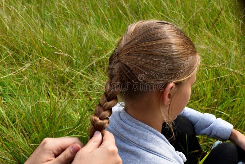 对女儿的母亲辫子头发的在夏天 免版税库存照片