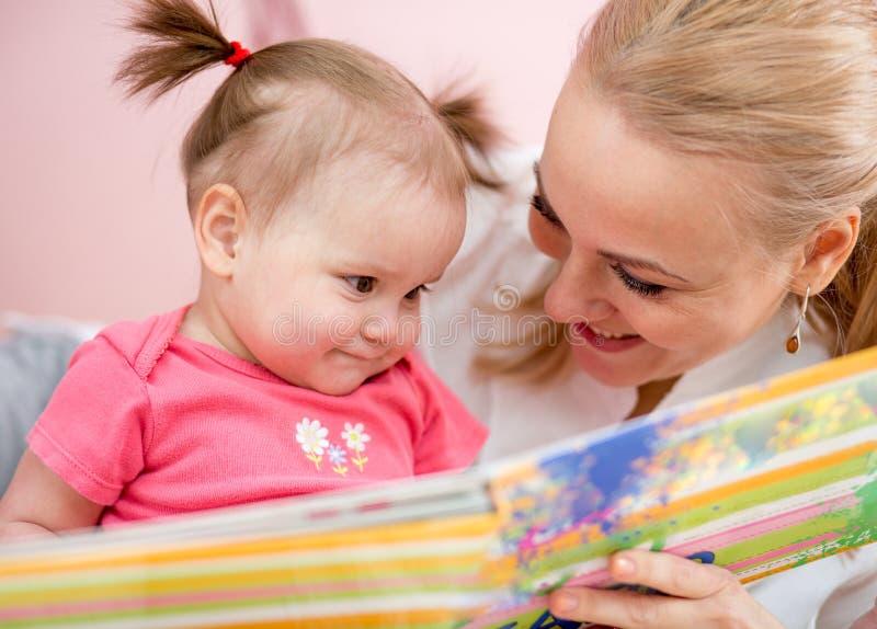 对女婴的愉快的妈妈阅读书户内 免版税库存图片