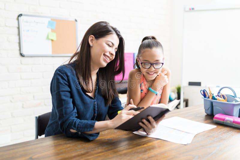 对女孩的确信的母亲阅读书在表上 免版税库存图片