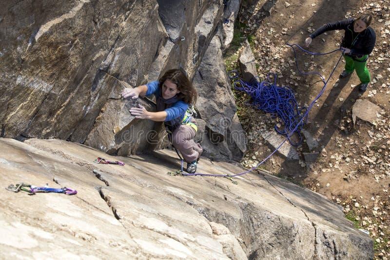 对女性登山人攻击岩石墙壁 库存照片