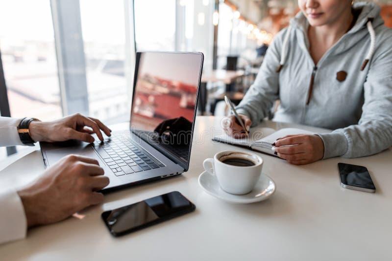 对她的上司的年轻女人谈话和在笔记薄的作为笔记 两人在咖啡馆坐在白色桌上用咖啡 库存图片