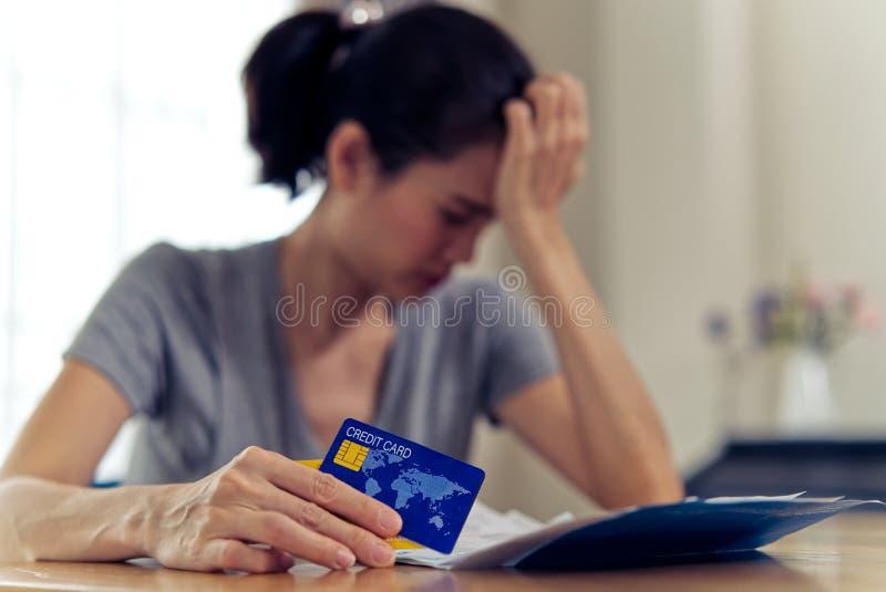 对她的信用的被注重的年轻坐的亚洲妇女忧虑 免版税库存图片