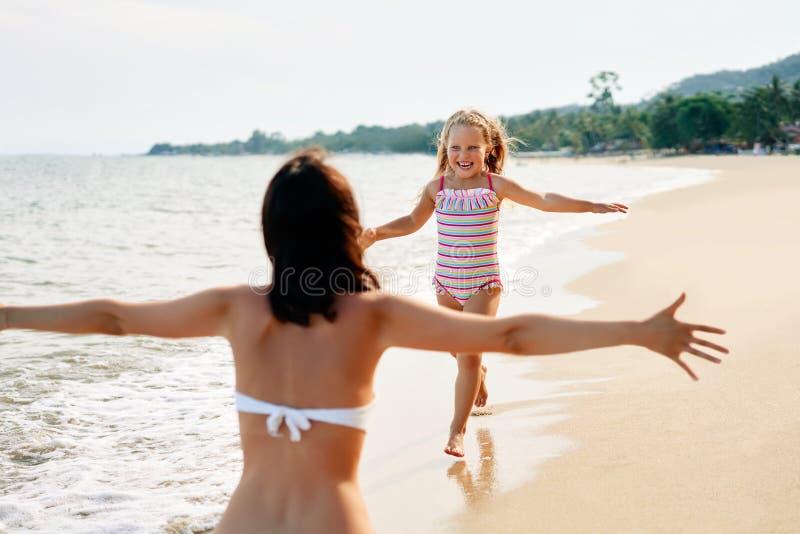 对她的母亲的愉快的女孩奔跑在热带海滩的拥抱的 库存图片