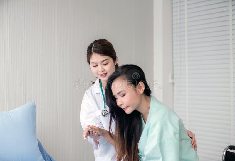 对她的耐心女性的亚洲医生支持医院,医疗保健概念,愉快的和微笑 免版税库存图片