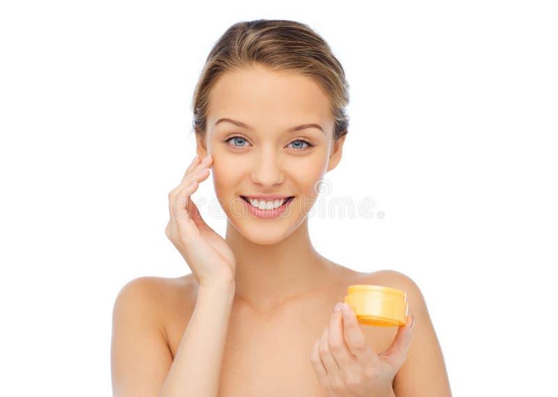对她的面孔的愉快的少妇appying的奶油 库存图片