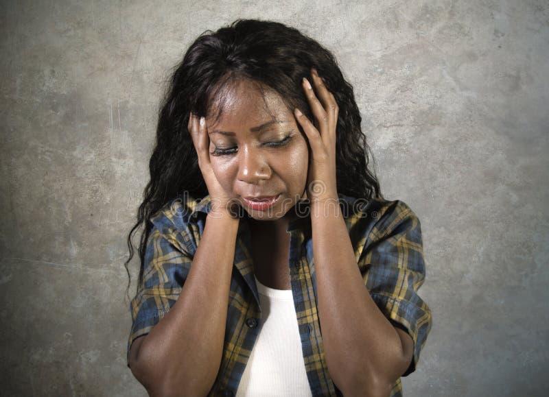 对她的顶头感觉负的年轻哀伤和沮丧的黑人非裔美国人的妇女病态和注重在演播室背景suff 免版税库存照片