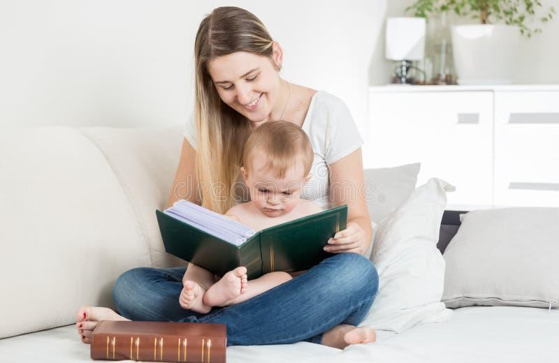 对她的9个月的微笑的母亲读书故事男婴 库存照片