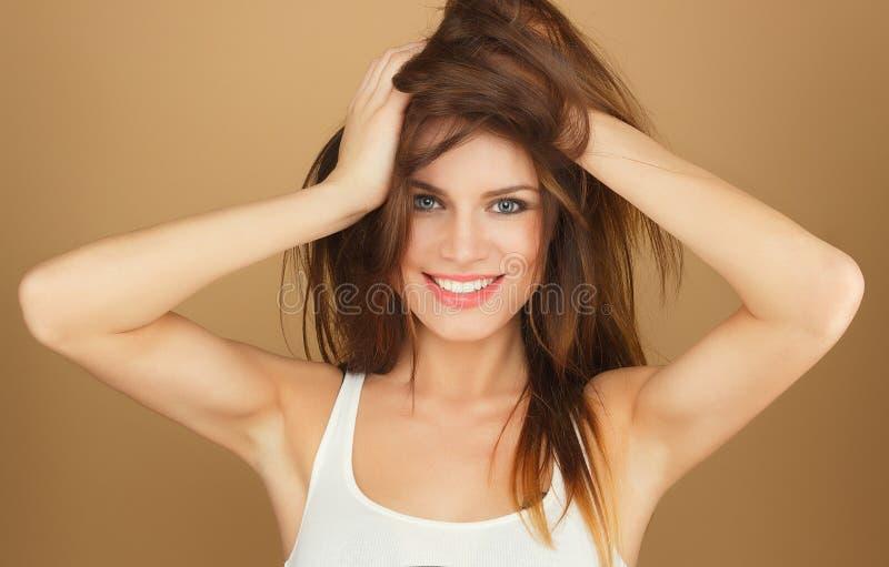 紧贴对她的头发的一件白色T恤杉的美丽的女孩 免版税库存图片